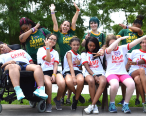 Campers and counselors taking a silly cabin photo at Camp Spike N Wave. Become a camp angel to sponsor campers.