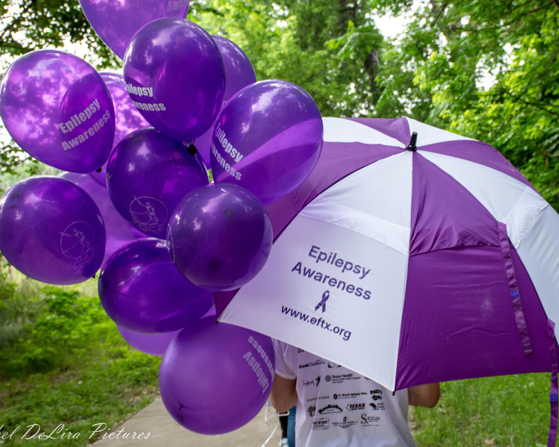 "Purple and white umbrella and purple balloons that both say ""Epilepsy Awareness"""