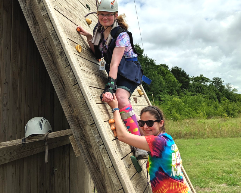 Kamp Kaleidoscope counselor helping camper climb rock wall